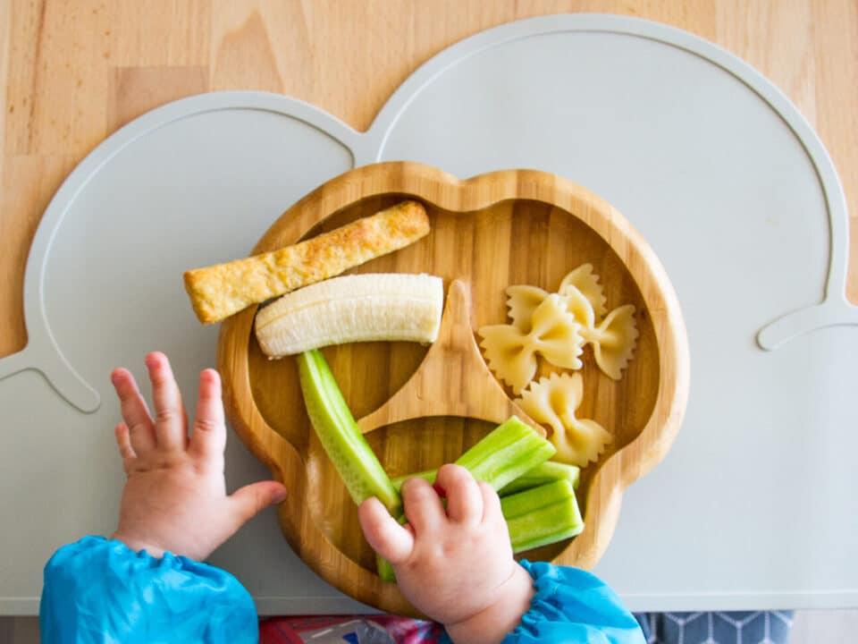 mãos de um bebê adepto ao BLW seguram alimentos em pedaços sob o pratinho de comida.
