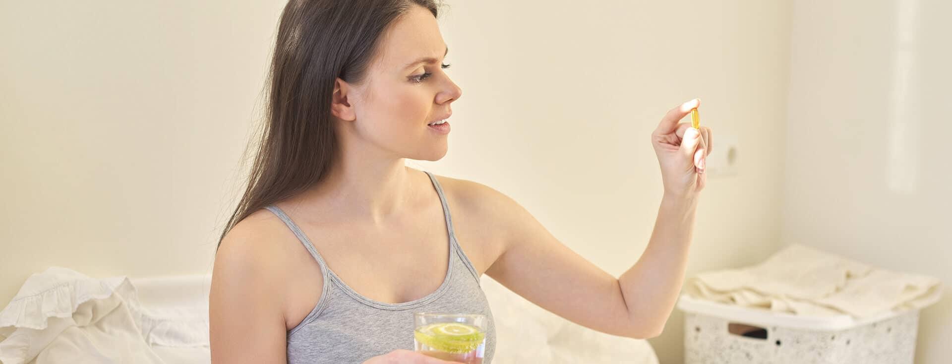 Mulher grávida tomando seu suplemento de ômega 3.