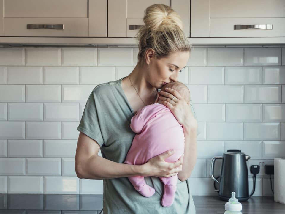 jovem mãe segura bebê contra o peito, com ternura, na cozinha